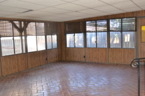 The closed in patio that we will be tearing out (well, we'll keep the tile and patio cover, but the walls have to go)