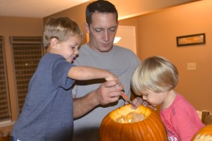 Boys help Dad prepare the pumpkin for carving