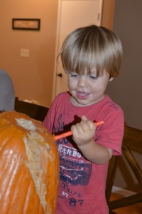 Austin carving a lid for his pumpkin