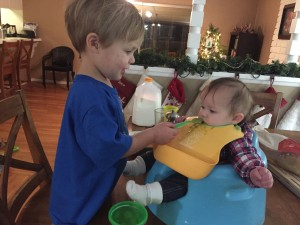 Austin helps feed Audrey her first solid food