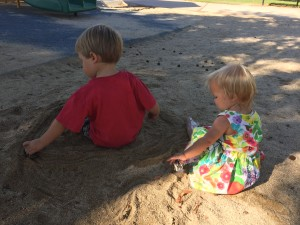 Austin and Audrey racing their cars together at the park